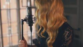 Ο όμορφος αοιδός τζαζ στο φόρεμα με φωτεινό αποτελεί το γέλιο στη σκηνή στο μικρόφωνο φιλμ μικρού μήκους