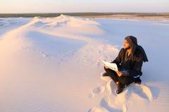 Ο όμορφος αραβικός αρσενικός αρχιτέκτονας εξετάζει τα έγγραφα και κάθεται στο sa Στοκ Φωτογραφία