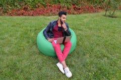 Ο όμορφος αραβικός νέος επιχειρηματίας κάθεται με το lap-top στην έδρα, κοιτάζει Στοκ Εικόνες
