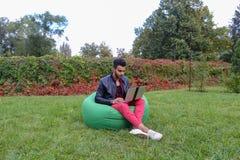 Ο όμορφος αραβικός νέος επιχειρηματίας κάθεται με το lap-top στην έδρα, κοιτάζει Στοκ Φωτογραφίες