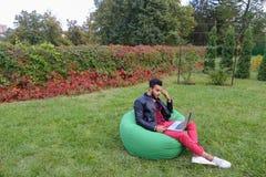 Ο όμορφος αραβικός νέος επιχειρηματίας κάθεται με το lap-top στην έδρα, κοιτάζει Στοκ εικόνα με δικαίωμα ελεύθερης χρήσης