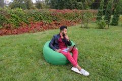 Ο όμορφος αραβικός νέος επιχειρηματίας κάθεται με το lap-top στην έδρα, κοιτάζει Στοκ φωτογραφίες με δικαίωμα ελεύθερης χρήσης