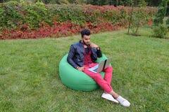 Ο όμορφος αραβικός νέος επιχειρηματίας κάθεται με το lap-top στην έδρα, κοιτάζει Στοκ Φωτογραφία