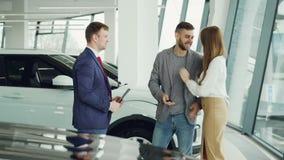 Ο όμορφος αρσενικός αγοραστής αυτοκινήτων παίρνει τη βασική αλυσίδα ρολογιού από το φιλικό πωλητή και τινάζει τα χέρια με τον που απόθεμα βίντεο