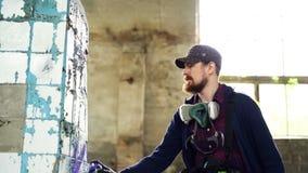 Ο όμορφος αστικός καλλιτέχνης τύπων είναι απασχολημένος με τη βρώμικη χαλασμένη στήλη στο εγκαταλειμμένο σπίτι με το χρώμα earoso απόθεμα βίντεο