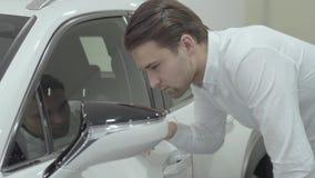 Ο όμορφος βέβαιος επιχειρηματίας πορτρέτου επιθεωρεί το πρόσφατα αγορασμένο αυτοκίνητο από τη εμπορία αυτοκινήτων Αίθουσα εκθέσεω απόθεμα βίντεο
