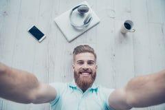 Ο όμορφος γενειοφόρος νεαρός άνδρας κάνει selfie και χαμογελά Είναι Στοκ Εικόνες