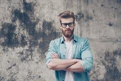 Ο όμορφος γενειοφόρος νεαρός άνδρας Nerdy στέκεται κοντά στο outdo τοίχων Στοκ Εικόνες