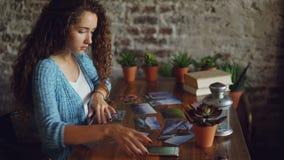 Ο όμορφος δημιουργικός σχεδιαστής κοριτσιών βάζει τις φωτογραφίες στον ξύλινο πίνακα πυροβολώντας έπειτα το επίπεδο βάζει τις εικ απόθεμα βίντεο