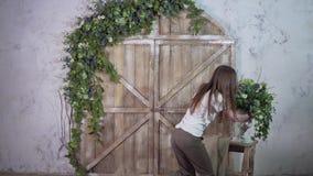 Ο όμορφος διακοσμητής κοριτσιών φέρνει ένα βάζο των λουλουδιών και βάζει σε μια εκλεκτής ποιότητας μικρή σκάλα ενάντια σε ένα όμο φιλμ μικρού μήκους