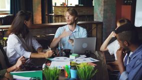 Ο όμορφος διευθυντής νεαρών άνδρων μιλά στους υπαλλήλους και τη gesturing συνεδρίασή του στο γραφείο στο σύγχρονο γραφείο Lap-top απόθεμα βίντεο