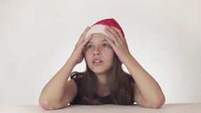 Ο όμορφος δυστυχισμένος έφηβος κοριτσιών σε ένα καπέλο Άγιου Βασίλη εκφράζει συναισθηματικά την απελπισία και αρχίζει να φωνάζει  απόθεμα βίντεο