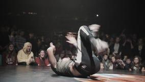 Ο όμορφος ενεργός τύπος στην γκρίζα μπλούζα και την ΚΑΠ δυναμικά στη σκηνή απόθεμα βίντεο