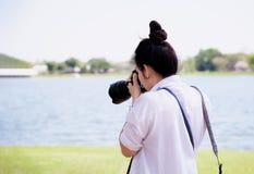 Ο όμορφος επαγγελματικός φωτογράφος γυναικών παίρνει τις εικόνες με DSLR Στοκ Εικόνες