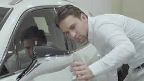 Ο όμορφος επιτυχής επιχειρηματίας πορτρέτου επιθεωρεί το πρόσφατα αγορασμένο αυτοκίνητο από τη εμπορία αυτοκινήτων Αίθουσα εκθέσε απόθεμα βίντεο