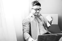Ο όμορφος επιχειρηματίας, κάθεται από την εφημερίδα ανάγνωσης παραθύρων ξενοδοχείων και τον καφέ κατανάλωσης Στοκ εικόνα με δικαίωμα ελεύθερης χρήσης