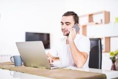 Ο όμορφος επιχειρηματίας μιλά στο κινητό τηλέφωνο και χαμογελά χρησιμοποιώντας ένα lap-top στην κουζίνα στοκ εικόνα