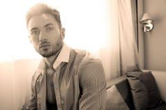 Ο όμορφος επιχειρηματίας που φορά το δεσμό και το ανοικτό πουκάμισο κάθεται μπροστά από το παράθυρο του δωματίου ξενοδοχείου στοκ φωτογραφίες