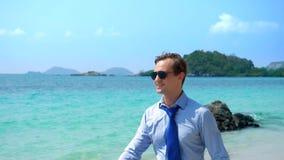 Ο όμορφος επιχειρηματίας στα γυαλιά ηλίου περπάτησε κατά μήκος μιας τροπικής παραλίας, που βγάζει το δεσμό του στοκ εικόνες