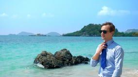 Ο όμορφος επιχειρηματίας στα γυαλιά ηλίου περπάτησε κατά μήκος μιας τροπικής παραλίας, που βγάζει το δεσμό του στοκ εικόνα
