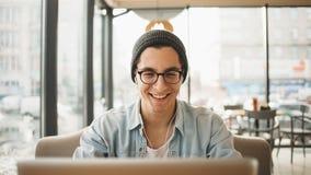 Ο όμορφος επιχειρηματίας στην περιστασιακή ένδυση και eyeglasses χρησιμοποιεί ένα lap-top στον καφέ στοκ εικόνες