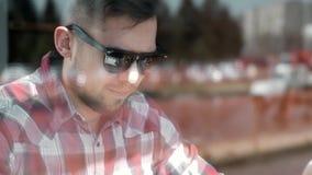 Ο όμορφος επιχειρηματίας στην περιστασιακή ένδυση και eyeglasses χρησιμοποιεί ένα lap-top που λειτουργεί στον καφέ Ο τύπος της Νί φιλμ μικρού μήκους