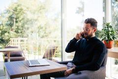 Ο όμορφος επιχειρηματίας eyeglasses χρησιμοποιεί ένα lap-top, που μιλά στο κινητό τηλέφωνο εργαζόμενος στην αρχή Στοκ φωτογραφίες με δικαίωμα ελεύθερης χρήσης