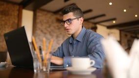 Ο όμορφος επιχειρηματίας freelancer στα γυαλιά που λειτουργούν επιμελώς στο lap-top στον καφέ αποσπά συνεχώς με την ενόχληση απόθεμα βίντεο