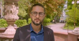 Ο όμορφος επιχειρηματίας hipster φορά eyeglasses με το ponytail και χαμογελά στη κάμερα που είναι θετική στο πάρκο φιλμ μικρού μήκους