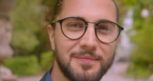 Ο όμορφος επιχειρηματίας hipster eyeglasses με το ponytail χαμογελά στη κάμερα που είναι θετική και κατάπληκτη στο πάρκο απόθεμα βίντεο