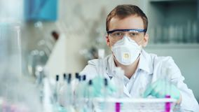 Ο όμορφος ερευνητής στο άσπρο παλτό εξετάζει τη κάμερα καθμένος στο εργαστήριο απόθεμα βίντεο