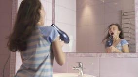 Ο όμορφος ευτυχής έφηβος κοριτσιών ξεραίνει την τρίχα με το στεγνωτήρα τρίχας και τραγουδά και χορεύει μπροστά από έναν καθρέφτη  απόθεμα βίντεο