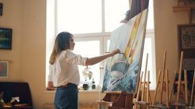 Ο όμορφος ζωγράφος κοριτσιών αναμιγνύει τα χρώματα στην παλέτα χρωματίζοντας έπειτα seascape στον καμβά που δημιουργεί την όμορφη απόθεμα βίντεο