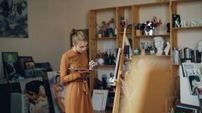 Ο όμορφος ζωγράφος κοριτσιών εργάζεται στη μόνες παλέτα και τη βούρτσα εκμετάλλευσης εργαστηρίων και εξετάζει τον καμβά Επάγγελμα απόθεμα βίντεο
