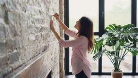 Ο όμορφος ιδιοκτήτης σπιτιών brunette διακοσμεί την κρεμώντας εικόνα δωματίων ύφους σοφιτών της στο τουβλότοιχο επιλέγοντας τη θέ φιλμ μικρού μήκους