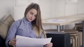 Ο όμορφος διευθυντής κοιτάζει μέσω των φύλλων του εγγράφου με το analytics στην αρχή απόθεμα βίντεο