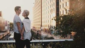 Ο όμορφος ισπανικός άνδρας και η καυκάσια γυναίκα στέκονται τα χέρια, εξετάζοντας ο ένας τον άλλον στη γέφυρα ηλιοβασιλέματος πόλ φιλμ μικρού μήκους