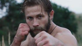 Ο όμορφος ισχυρός αθλητής εξετάζει τη κάμερα και παρουσιάζει πυγμές του αργά απόθεμα βίντεο