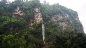 Ο όμορφος καταρράκτης χύνει από το βράχο στα βουνά με τα πυκνά αειθαλή δάση φιλμ μικρού μήκους