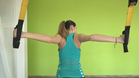 Ο όμορφος καυκάσιος επαγγελματικός εκπαιδευτής κοριτσιών εκτελεί τις δύσκολες ασκήσεις στις αρθρώσεις TRX φιλμ μικρού μήκους