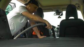 Ο όμορφος κύριος στη μαύρη ΚΑΠ σκουπίζει το ενεργά γκρίζο αυτοκίνητο με ηλεκτρική σκούπα φιλμ μικρού μήκους