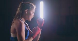 Ο όμορφος μαχητής γυναικών στους κόκκινους επιδέσμους διευθύνει μια πάλη σκιών ασκώντας στη γυμναστική κίνηση αργή steadicam πυρο απόθεμα βίντεο