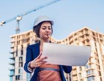 Ο όμορφος μηχανικός επιχειρησιακών γυναικών στέκεται με τα έγγραφα σχεδίων στοκ φωτογραφία