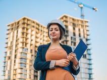 Ο όμορφος μηχανικός επιχειρησιακών γυναικών στέκεται με τα έγγραφα σχεδίων στοκ εικόνες