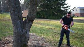Ο όμορφος μισθωμένος ανάδοχος προετοιμάζεται να περιορίσει ένα δέντρο με το αλυσιδοπρίονο φιλμ μικρού μήκους