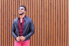 Ο όμορφος νέος αραβικός τύπος θέτει στη κάμερα, ισιώνει το σακάκι Στοκ φωτογραφία με δικαίωμα ελεύθερης χρήσης
