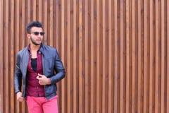 Ο όμορφος νέος αραβικός τύπος θέτει στη κάμερα, ισιώνει το σακάκι Στοκ Εικόνες