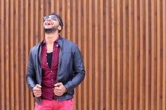 Ο όμορφος νέος αραβικός τύπος θέτει στη κάμερα, ισιώνει το σακάκι Στοκ εικόνες με δικαίωμα ελεύθερης χρήσης