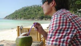 Ο όμορφος νέος επιχειρηματίας στα γυαλιά ηλίου πίνει το φρέσκο χυμό καρύδων σε έναν καφέ παραλιών με την άποψη θάλασσας σχετικά μ απόθεμα βίντεο