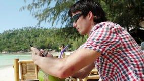 Ο όμορφος νέος επιχειρηματίας στα γυαλιά ηλίου σε έναν καφέ παραλιών με την άποψη θάλασσας σχετικά με το υπόβαθρο χρησιμοποιεί το απόθεμα βίντεο